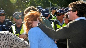 Protester Anthony Main grabs fellow protester Mel Gregson hair and head as she screams police brutality.  Police set up to protect drill workers in Alexander Parade, Fitzroy.  The drillers are taking core samples for the East West link Tunnel.    Pic. Nicole Garmston