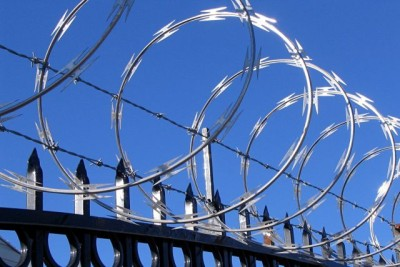 barbed and razor wire on top of fence