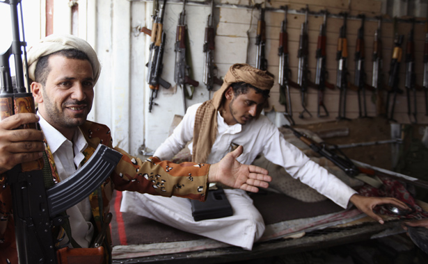 Man gestures whilst holding a gun at a weapons store in a market in Arhab